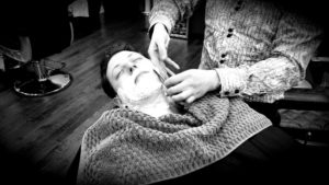 Picture of a barber shaving beard of client