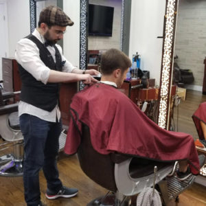 Picture of a barber trimming hairs