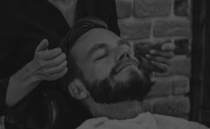 Picture of a man laying head on chair in barbershop