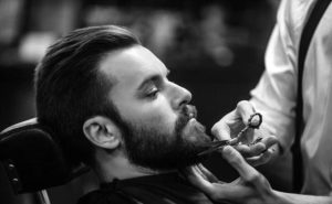 Picture of a barber cutting beard hairs of client