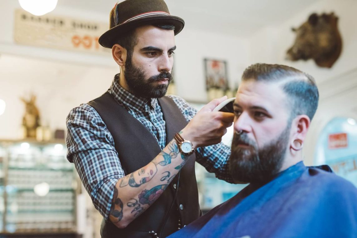 Picture of a barber trimming hairs of client